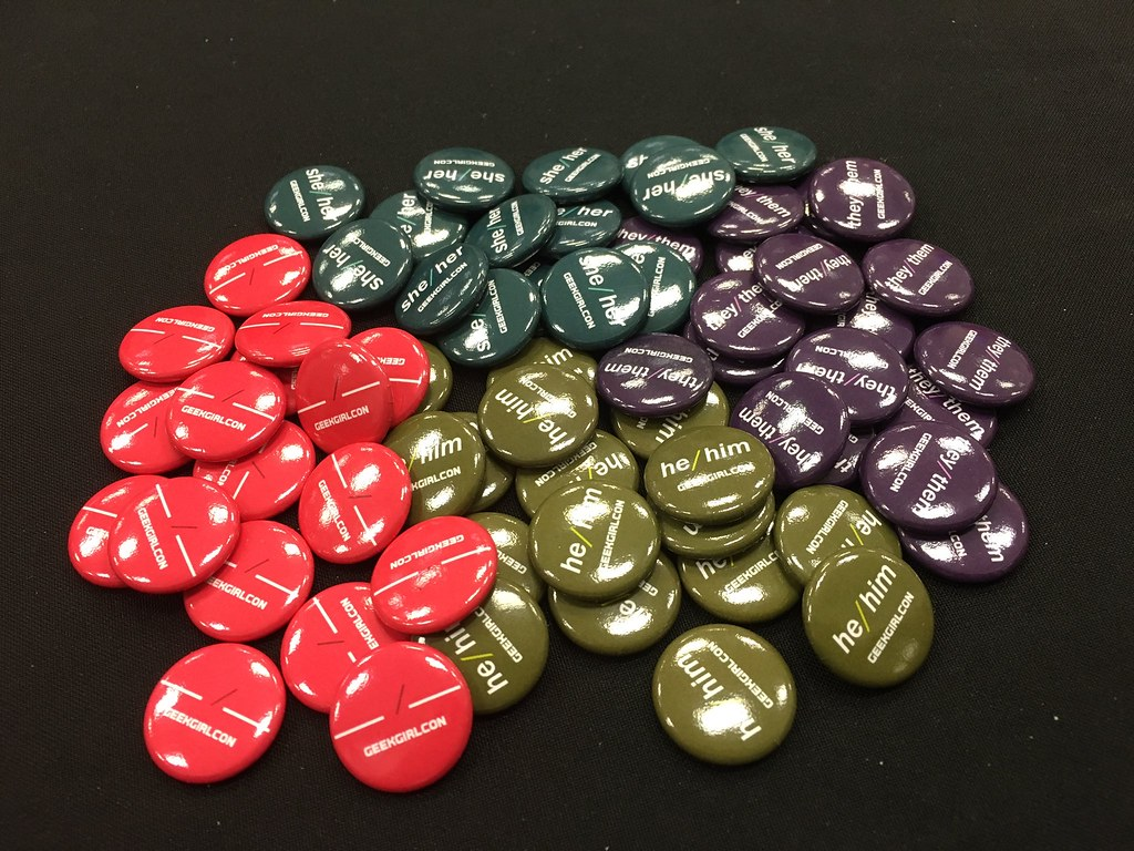 A pile of pronoun pins in different colors.