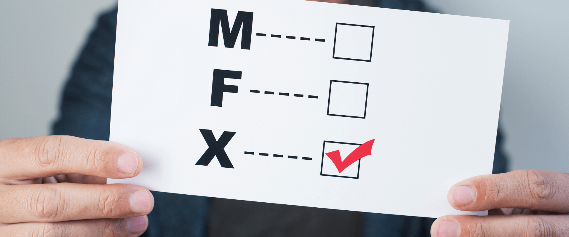 Person holding a sign with options M, F and X. Option X is checked in red.